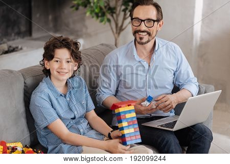 poster of Pleased with results. Lovely wavy-haired boy sitting on the sofa next to his father and showing a new tower constructed with an erector set while both of them looking content with the result