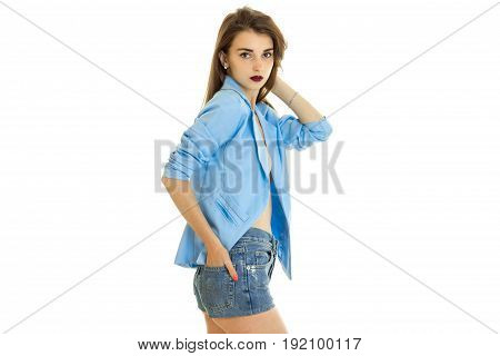Beautiful woman in blue jacket without underwear looks at the camera isolated on white background