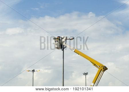 The electrical technician man on the basket of the lifting car.Street lamp maintenance .
