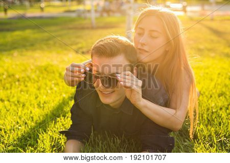 fun and love concept with a young couple lying down in grass and smiling.