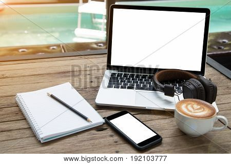 office stuff with laptop coffee cup notepad smartphone and headphone on wood table at poolside