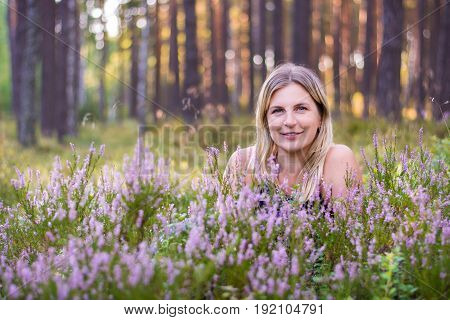Beautiful young woman lies in a heather field. The photo was taken in the summer, not long before sunset. Beautiful sunset background in a quiet forest.
