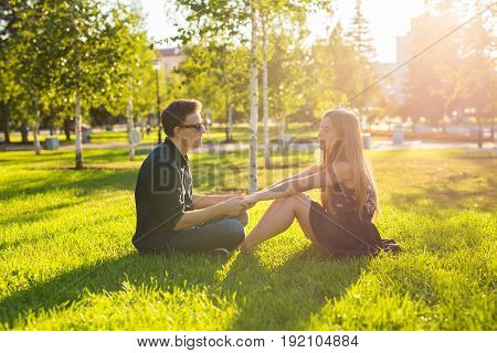 Friendship and love concept with a young couple sitting on the grass and talking