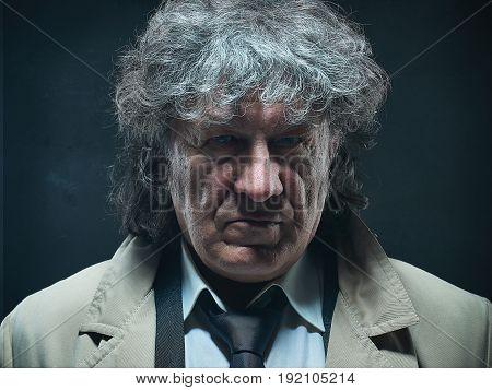The senior man in cloak as detective or mafia boss. Studio shot on gray in retro stile. The male face close up
