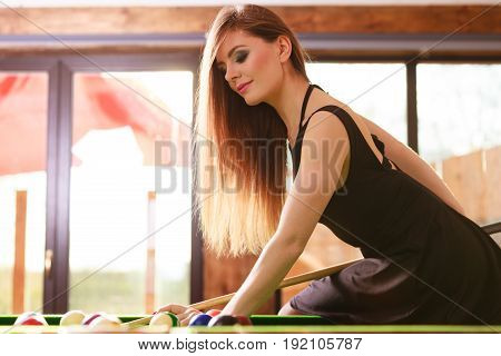 Competition concept. Young focused girl having fun with billiard. Pretty fashionable woman spending time on playing rivalry.