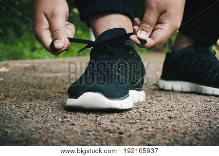 Athlete ties up shoelaces on sneakers before training in the open air, sporty lifestyle concept