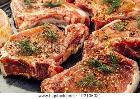 Raw uncooked juicy steak meat with dill, pepper and spices on the side, before cooking