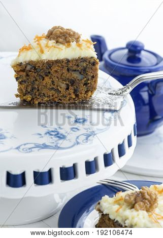 slice of moist carrot cake with walnuts on a blue and white cake stand with a sliver cake slice and fork, copy space in foreground and background