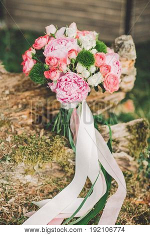 Beautiful wedding bouquet on the grass with wooden background