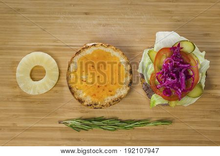 Open burger with pineapple, onion and vegetables, top view