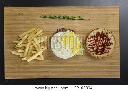 Uncovered tasty burger with fried eggs and potato's on the table, view from top