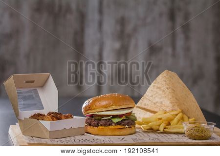 Delicious hamburger lunch with potatoes and fried chicken, on the table