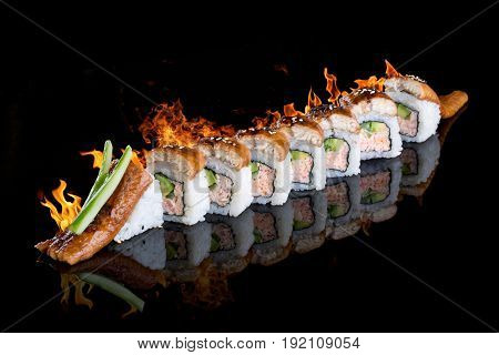 Roll Dragon with fire. On a black background with reflection