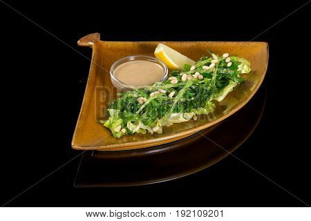 Salad with seaweed and peanut sauce. On a black background with reflection.