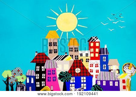 Fabric town. Houses trees and the sun made of colorful pieces of fabric isolated on blue background.