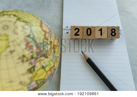 2018 world travel goal concept with wooden blocks number and pencil on white note paper.