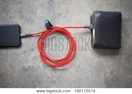 Conceptual image of expensive smartphone costs presented with power cable credit cards and wallet.
