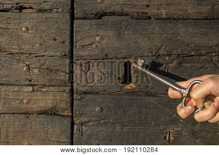 woman hand holding a key with vintage keyhole on wooden door.