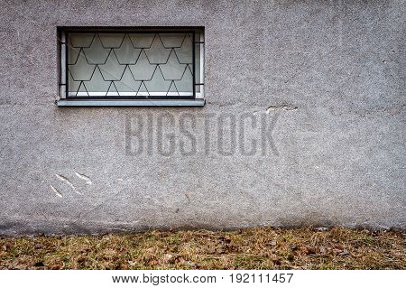 Concrete wall with a window and ground. Architecture background