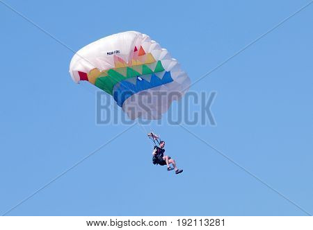 Male Sky Diver With Brightly Coloured Open Parachute Preparing For Landing