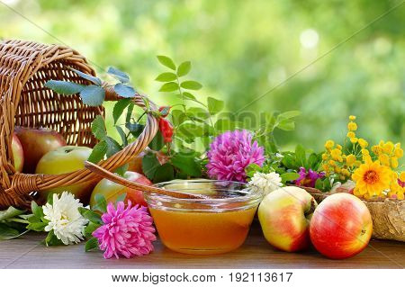Flower honey, apples and garden flowers. Summer still life. Blurred background.