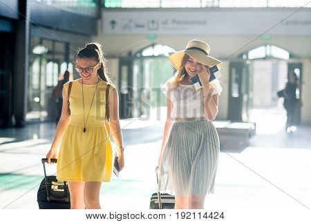 Charming young tourists at the station. In hands baggage tickets passports. Summer holiday. Excellent mood.