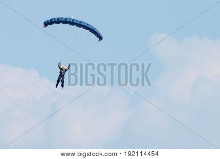 Sky Diver Against Clouds With Brigh Blue Open Parachute - Text Area Available