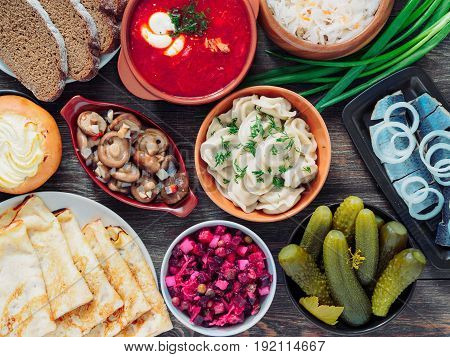 Top view of wooden table with dishes of russian cuisine - borscht, pelmeni, herring, marinated mushrooms, salted cucumbers, vinaigrette, sauerkraut, rye bread, pancakes, cheese pastry. Top view