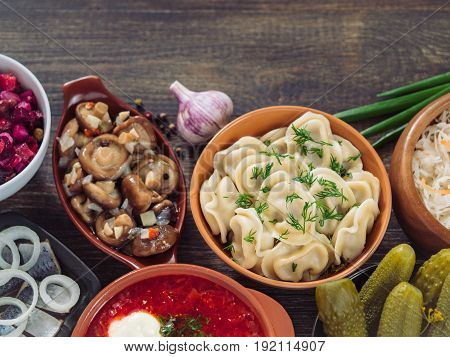 Russian food with copy space. Assortment dishes of Russian cuisine - borscht, pelmeni, herring, marinated mushrooms, salted cucumbers, vinaigrette, sauerkraut and pancakes. Top view or flat lay