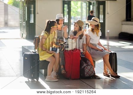 Company of young tourists in the waiting room at the station. Girls sit on a bench. Near them there is their baggage. Girlfriends briskly discuss something. Good mood. Summer tourism.