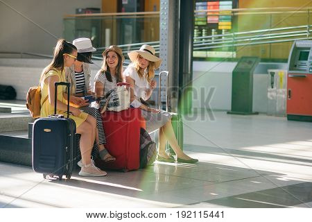Company of young tourists in the waiting room at the station. Girls sit on a bench. Near them there is their baggage. Girlfriends briskly discuss something. Anticipation of an interesting travel.