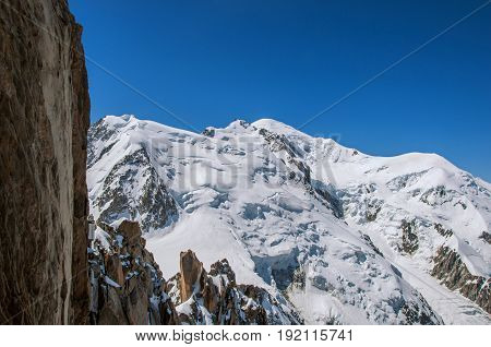 View of the Mont Blanc and rocks from the Aiguille du Midi, in French Alps Chamonix Mont Blanc, alpine mountains landscape, clear blue sky in warm sunny summer day