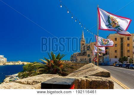 Festively decorated street with flags of all the Grand Masters of the Sovereign Military Order of Malta in the old town of Valletta, Malta