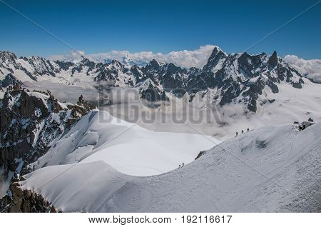 View of snowy peaks and mountaineers from the Aiguille du Midi, in French Alps Chamonix Mont Blanc, alpine mountains landscape, clear blue sky in warm sunny summer day. Retouched photo