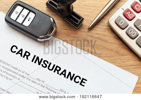 Top view of car insurance lay down on wooden desk with car key rubber stamp and calculator.