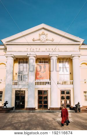 Gomel, Belarus - March 17, 2017: Old Woman Walking Near Building Of Gomel Puppetry Theatre Theater On Pushkin Street In Sunny Spring Day.