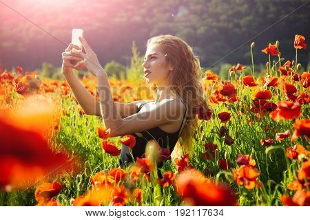 girl with long curly hair in black vest making selfie photo by mobile phone in flower field of red poppy seed with green stem on natural background summer spring drug and love intoxication opium