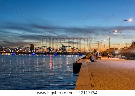 Riga, LV - AUGUST 10, 2016: Riga promenade near Daugava river at sunset