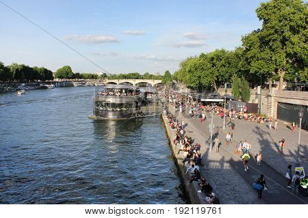 PARIS, FRANCE - JUNE 5, 2016: People walk along on Seine river embankment waterfront and tourist cruise boat view on summer day. French capital is the most visited city in the world.