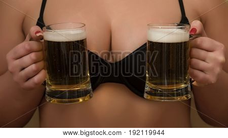 glass mugs with light beer or lager with foam in female hands on sexy black bra supporting female breast or bust. Alcohol and refresher. Bad habits addiction and desire