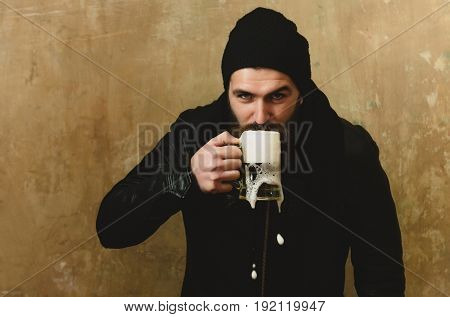 man or bearded hipster with long beard and moustache drinking beer with foam from glass mug in black hat and jacket on beige wall. Alcohol bad habits addictive lifestyle refresher convive
