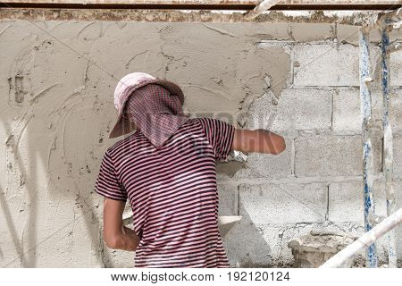 Man Pressing An Cement Tile Into A Glue On A Wall.