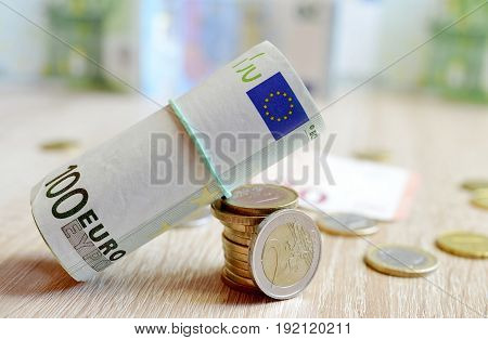 Euro coins and banknote on wooden board.
