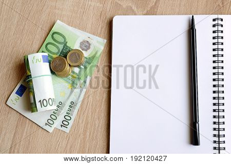 Office desk table with pen,notebook and money. Financial and investment concepts.
