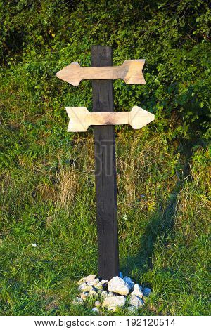 Old wooden pole with two wooden planks in form of arrows for inscriptions. Wooden directional sign with two empty arrows