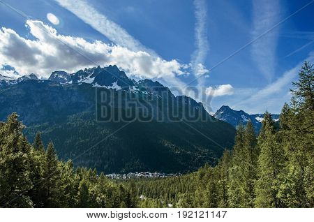 Forest in Argentière with snowy mountains and village in the background, blue sky with clouds, French Alps