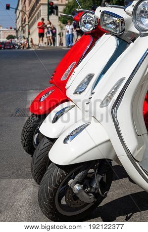 Scooters parked in a row on the edge of the road. Red / White Scooters.