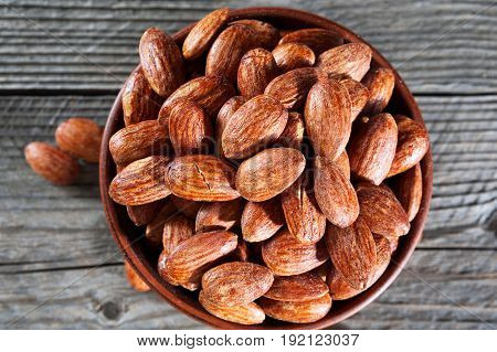 Top View Of Hickory Smoked Almonds In A Small Bowl On A Wood Table.