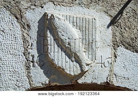 Heraldic shield carved in stone with fish and date in the historical city center of Annecy. Located in the department of Haute-Savoie, Auvergne-Rhône-Alpes region, in south-eastern France