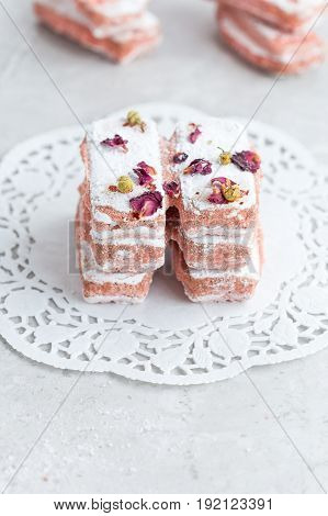 Afternoon Tea of Pink Biscuits on White Vintage Doily on Grey Marble Table